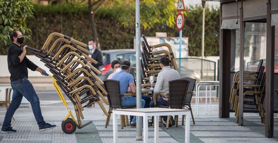 Camareros de un bar recogen el mobiliario para proceder al cierre. EFE/José Manuel Vidal
