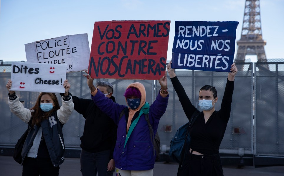 Cuatro manifestantes exhiben pancartas contra la violencia policial y el proyecto de ley de seguridad global en París. EFE/EPA/Ian Langsdon