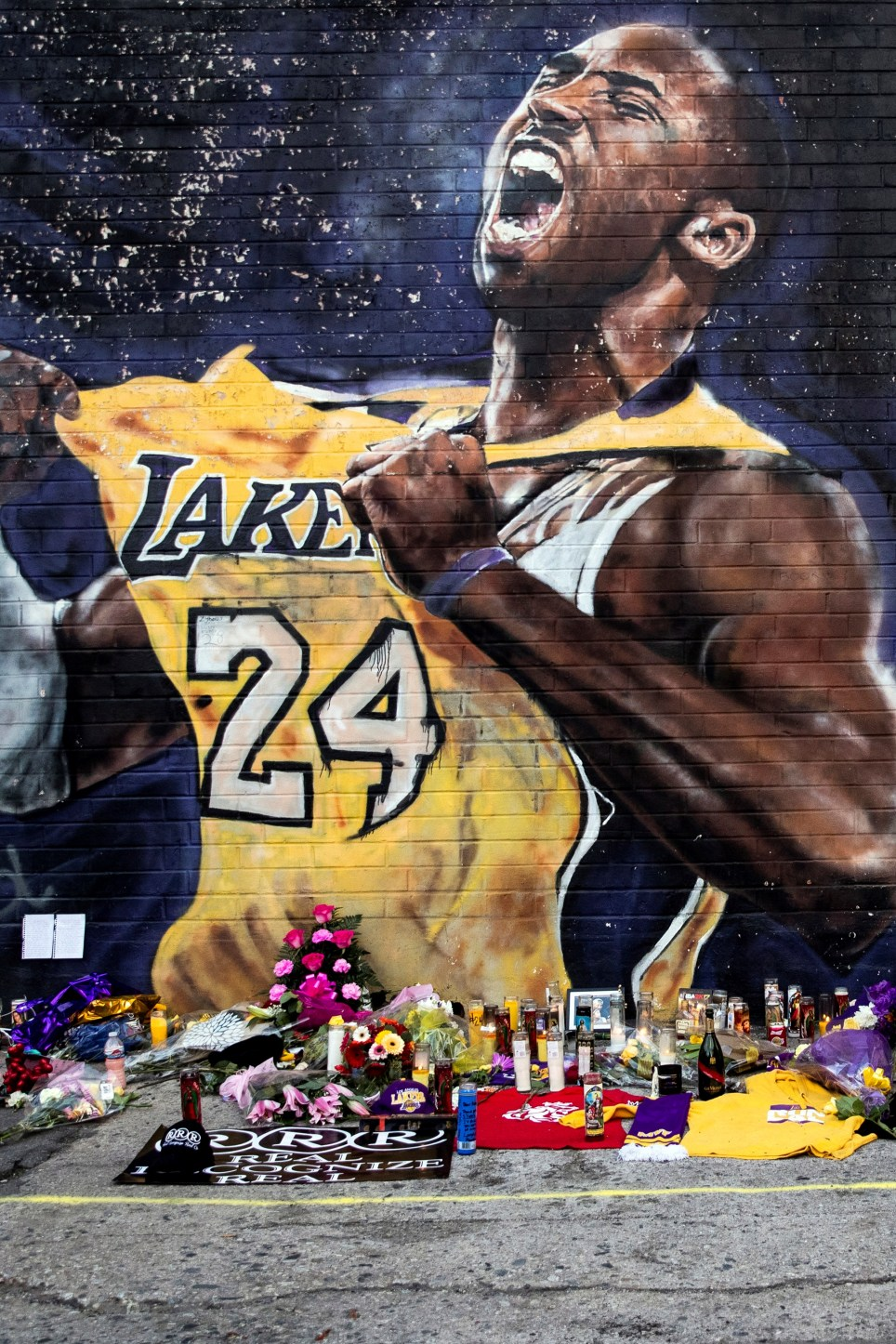 Flores y velas junto a un mural que rinde homenaje a Kobe Bryant cerca del Staples Center, el estadio de Los Ángeles Lakers. EFE/Etienne Laurent