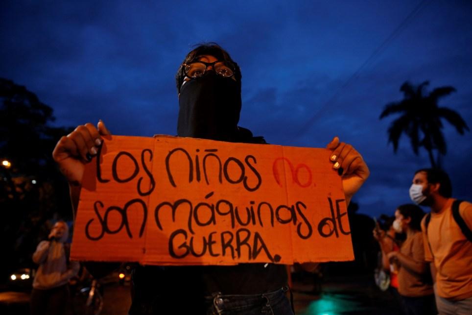 Una manifestante sostiene una pancarta de protesta alusiva a las polémicas declaraciones del ministro de Defensa colombiano, Diego Molano, durante un plantón contra el asesinato de menores de edad por parte del Estado, frente al Cantón Militar Pichincha en Cali (Colombia). EFE/ Ernesto Guzmán Jr/Archivo