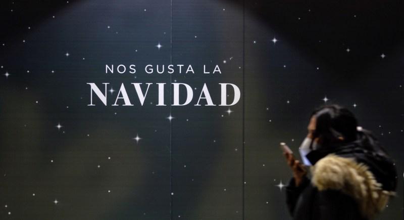 Una mujer pasa en Valladolid por delante del escaparate de una tienda que muestra un lema navideño. EFE/Nacho Gallego