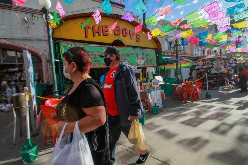 Una pareja de adultos mayores camina por una calle comercial en Tijuana, en el estado de Baja California (México). La alerta roja o de máximo riesgo de contagio por la pandemia se rencendió en el estado mexicano de Baja California, fronterizo con Estados Unidos, lo que obliga a suspender por segunda ocasión los sectores económicos no esenciales. La entidad mexicana, vecina de California, reporta un total de 27.122 casos positivos de covid-19, incluyendo este lunes al gobernador, Jaime Bonilla, al secretario de Economía, Mario Escobedo, y a la secretaria de Infraestructura, Karen Postlethwaite. EFE/Joebeth Terriquez/Archivo
