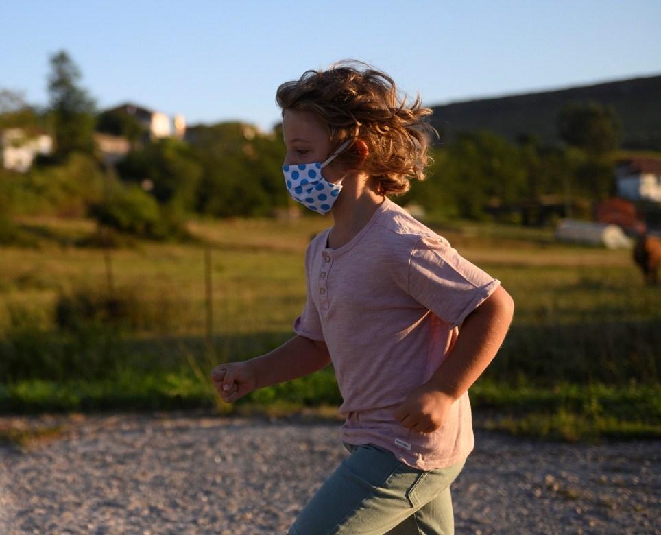 Un niño con mascarilla juega en Suances (Cantabria). EFE/Pedro Puente Hoyos
