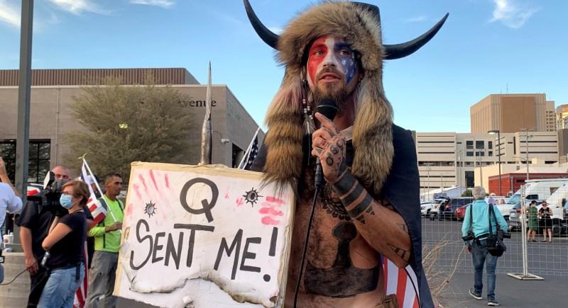 """Un miembro del movimiento QAnon habla disfrazado y con una pancarta que dice """"""""Q me envió"""""""" en Phoenix, Arizona (EEUU). EFE/ Álex Segura"""