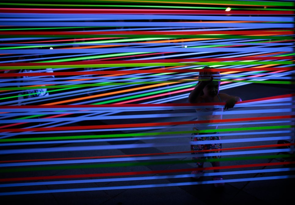 Una niña, en Singapur, mira a través de una instalación artística hecha con cables que reflejan el color ultravioleta. EFE/Wallace Woon