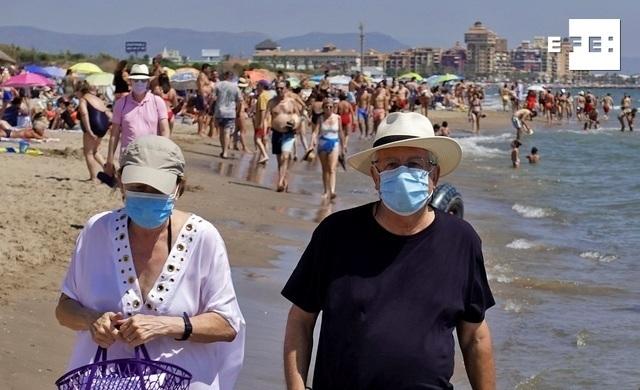 Dos personas pasean por la orilla de la playa de La Patacona de Alboraia, en Valencia, protegidos con mascarillas. EFE/Manuel Bruque