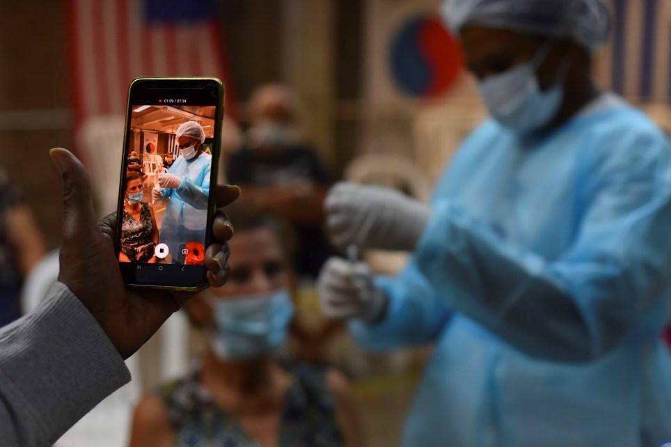 Un hombre graba con su celular el proceso de vacunación de una familiar en el estadio Pascual Guerrero de Cali (Colombia). EFE/ Ernesto Guzmán Jr/Archivo