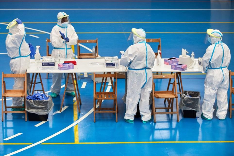Personal sanitario se prepara para realizar pruebas PCR a los vecinos del pueblo de Sant Joan de les Abadesses (Girona) durante un cribado masivo tras detectarse en el municipio cinco brotes de COVID-19. EFE/David Borrat.