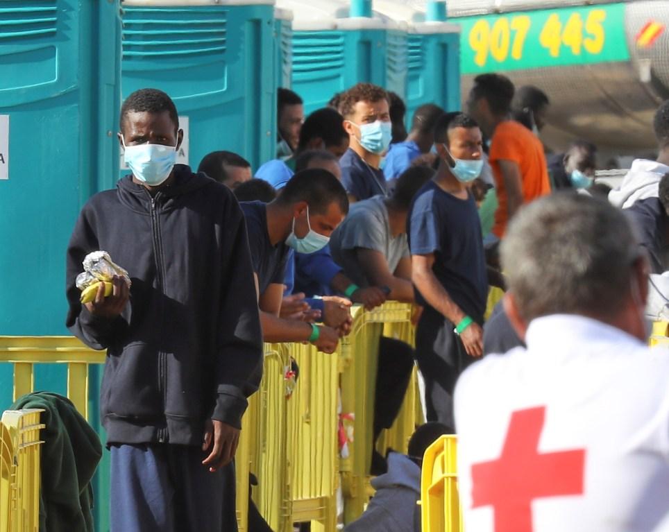 Inmigrantes en el muelle de Arguineguín, Gran Canaria, atendidos por Cruz Roja. EFE/Elvira Urquijo A.