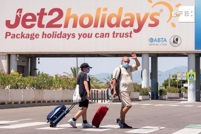 Varios turistas se dirigen a la terminal de salida del aeropuerto de Palma. EFE/Atienza.