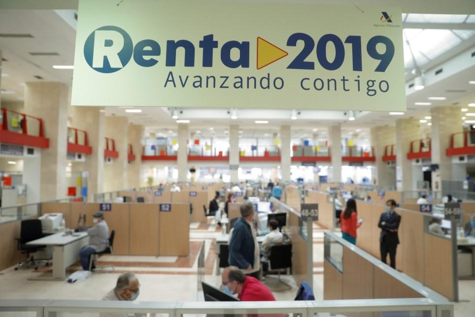Varios contribuyentes son atendidos en una sede madrileña de la Agencia Tributaria por la declaración de la renta de 2019. EFE/Emilio Naranjo