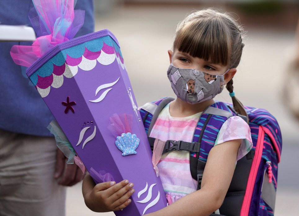 Una niña con mascarilla empieza el curso escolar en la localidad alemana de Taunusstein, en el estado de Hesse. EFE/EPA/Ronald Wittek.