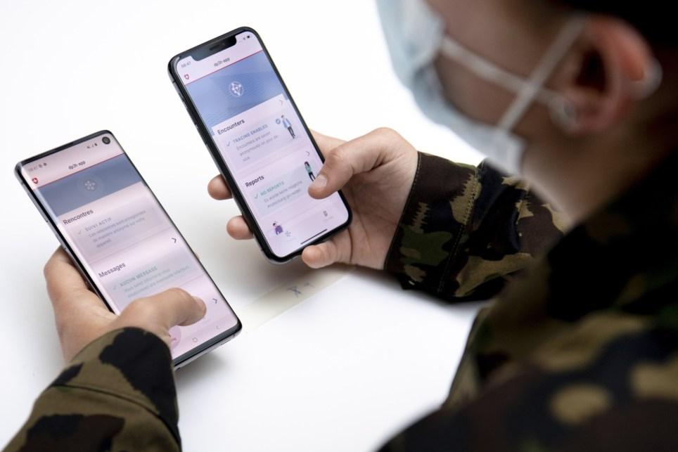 Un soldado suizo observa en Lausana dos teléfonos móviles, con sistemas operativos iOS y Android, durante la prueba de una aplicación para el rastreo de contagios frente a la COVID-19. EFE/EPA/LAURENT GILLIERON