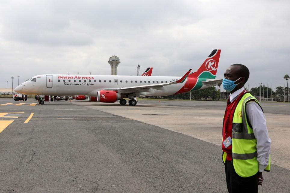 Un empleado de Kenya Airways espera junto a los dos primeros aviones que saldrán de Nairobi tras la reapertura del tráfico aéreo, que estaba suspendido por la pandemia. EFE/EPA/Daniel Irungu.