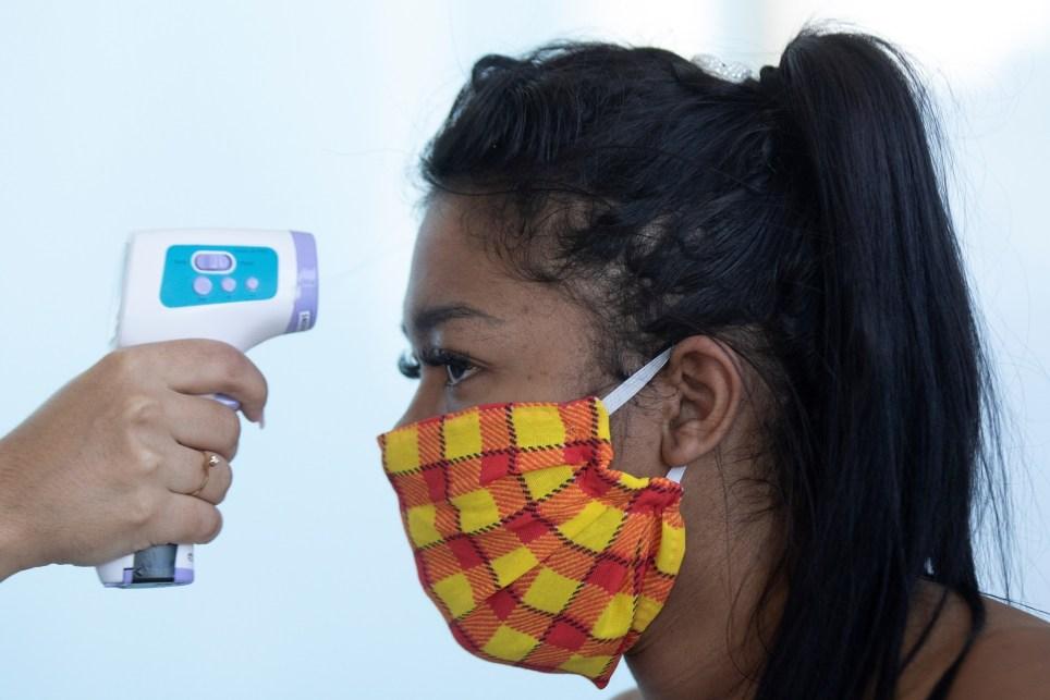 Una mujer con tapabocas se somete a un examen de temperatura en un centro comercial de Brasilia (Brasil). EFE/ Joédson Alves