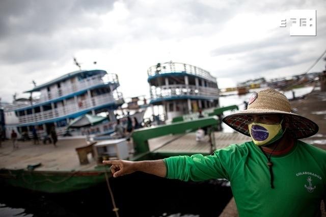 Un hombre con tapabocas de diseño de la bandera brasileña señala hacia el río Amazonas en Manaos (Brasil). EFE/ Raphael Alves
