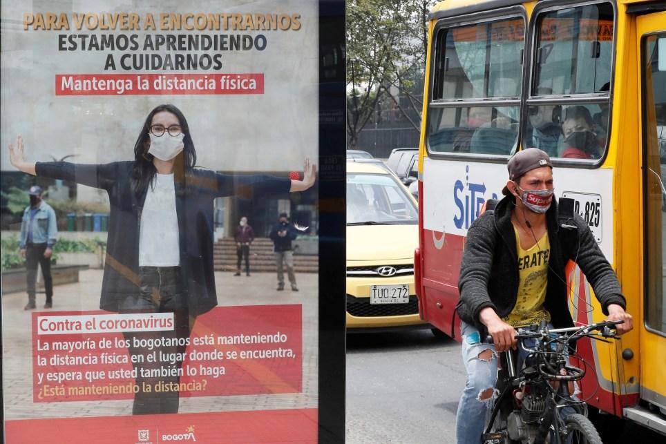 Un habitante de Bogotá pasa en bicicleta junto a un cartel con recomendaciones ciudadanas frente a la covid-19. EFE/ Carlos Ortega