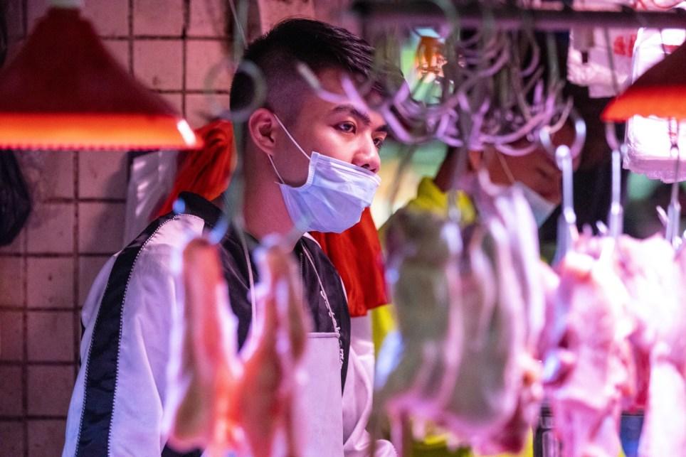 Un hombre vende carne con una mascarilla en un mercado de Guangzhou (China). EFE/EPA/Alex plavevski.