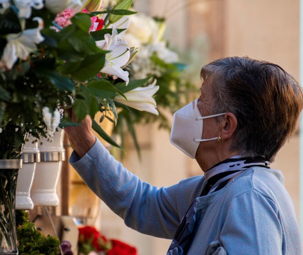 Una mujer adorna con flores un nicho en el cementerio mallorquín de Andratx. EFE/ Cati Cladera
