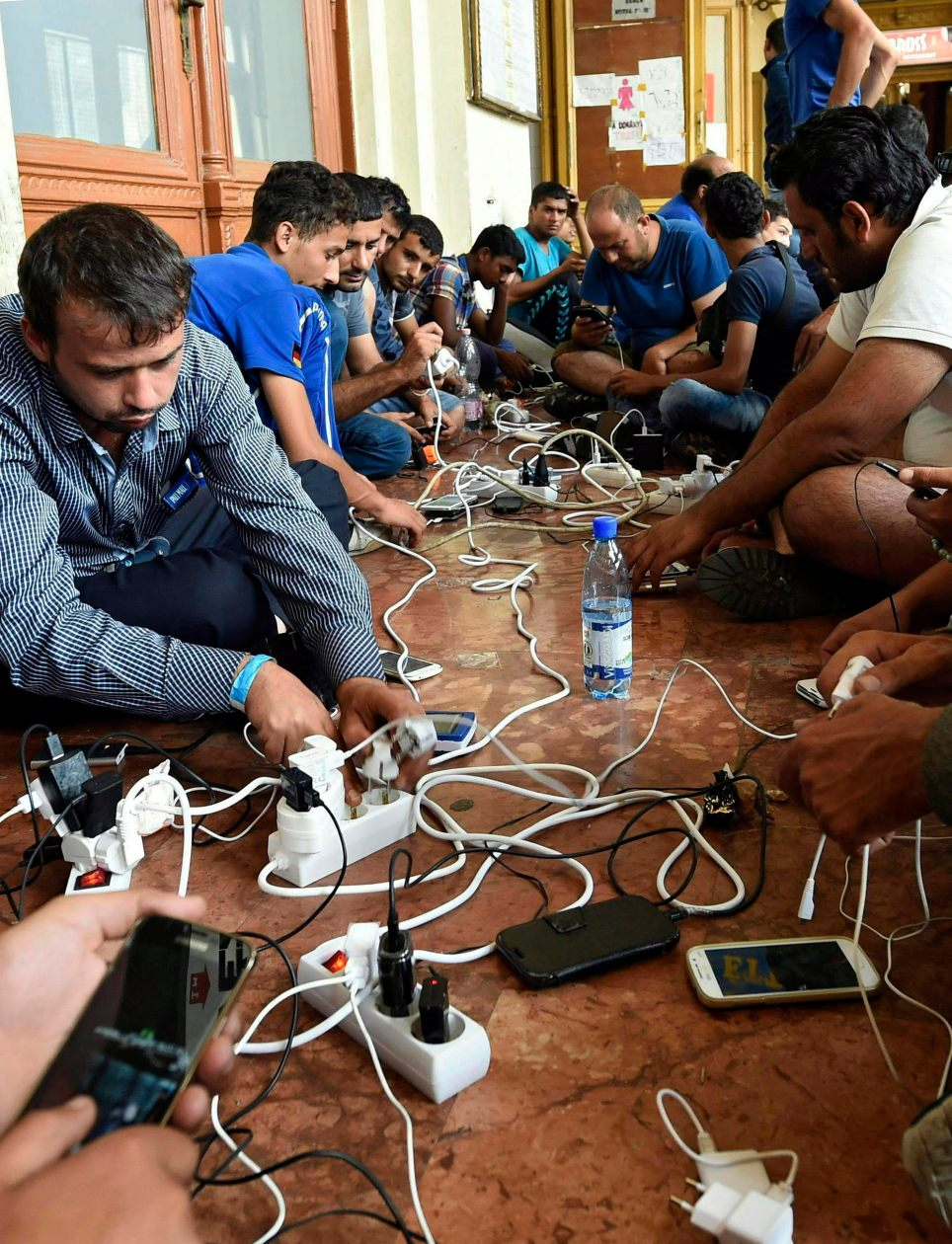 Refugiados cargan sus teléfonos móviles en la estación Keleti de Budapest en septiembre de 2015. EFE/HERBERT P. OCZERET