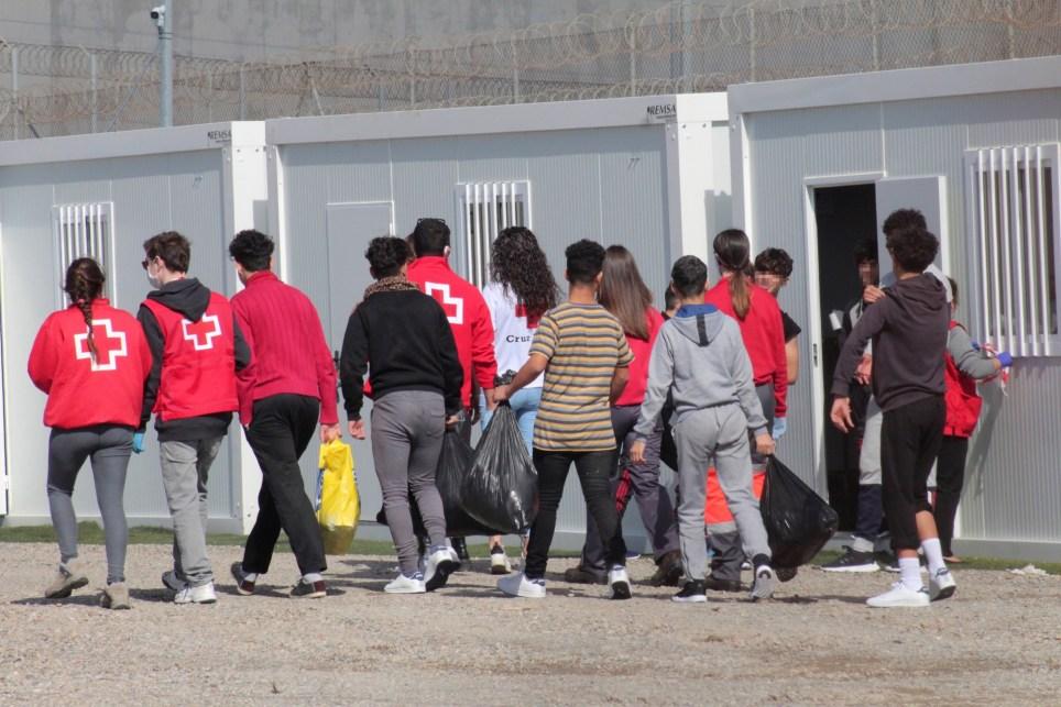 Varios menores extranjeros, acompañados por voluntarios de la Cruz Roja, llegan a un albergue provisional en Ceuta. EFE/Reduan