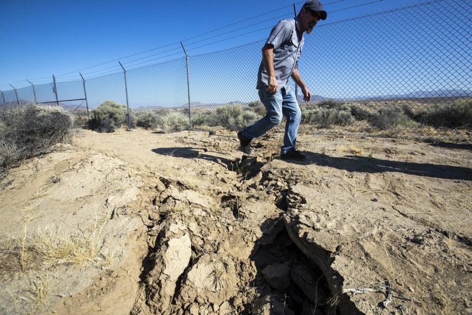 Un turista camina sobre una grieta abierta por un terremoto cerca de Ridgecrest, California, el 6 de julio de 2019. EFE/EPA/Etienne Laurent.