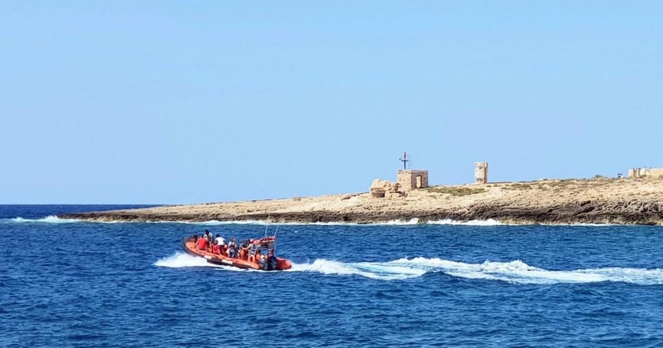 Una lancha con voluntarios de una ONG de rescates y salvamento navega frente a la isla italiana de Lampedusa. EFE/EPA/Elio Desiderio