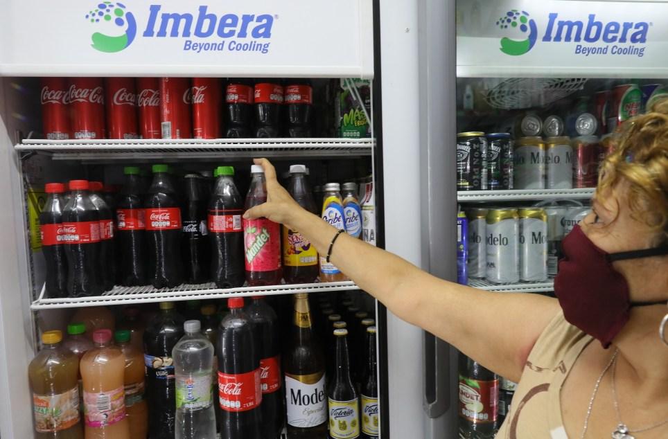 """MEX4689. CIUDAD DE MÉXICO (MÉXICO), 25/07/2020.- Una mujer compra bebidas azucaradas este sábado en una tienda de Ciudad de México (México). La tensión entre la industria de alimentos procesados y el Gobierno se ha agudizado con la pandemia en México, donde uno de cada cuatro muertos por la COVID-19 padecía obesidad, más de una tercera parte diabetes y casi la mitad hipertensión. Con 42.645 fallecidos en total, México es el cuarto país con más defunciones por la COVID-19 y el octavo con más letalidad, mayor al 11 %, un factor que el Gobierno atribuye a la alimentación heredada por el """"""""periodo neoliberal"""""""" y la industria de alimentos procesados. EFE/Alex Cruz"""