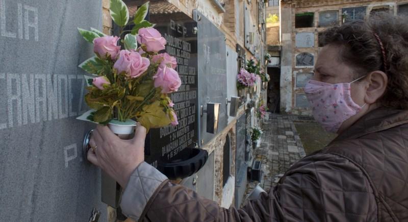 Una mujer coloca flores de plástico en la lápida de un familiar en el cementerio de San Eufrasio de Jaén. EFE/José Manuel Pedrosa.