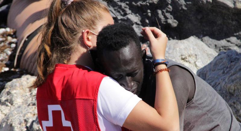 Abrazo de una voluntaria de Cruz Roja Española y uno de los migrantes que lograron entrar este martes en Ceuta desde Marruecos. EFE/Reduan