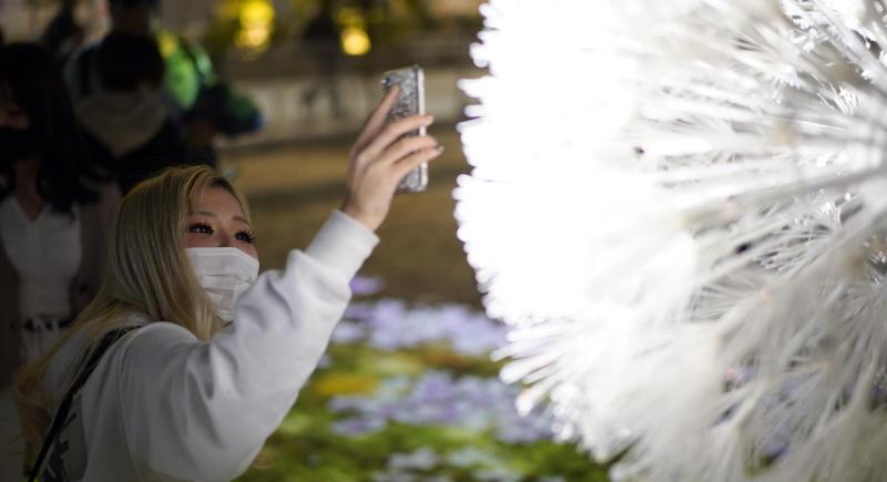 Una joven usa su teléfono inteligente en la exhibición de la instalación interactiva y digital 'Breath/Bless Project', en Tokio, Japón. EFE/EPA/FRANCK ROBICHON/Archivo