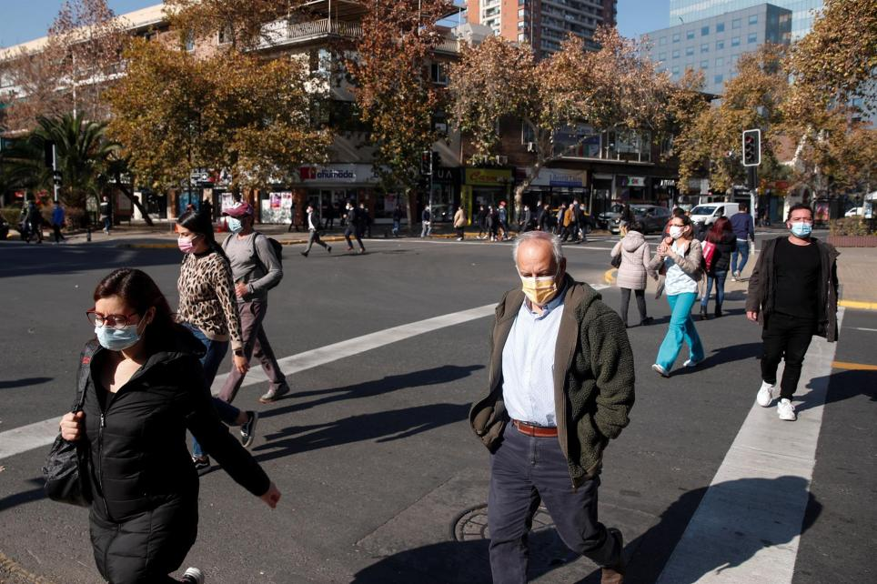 """Un grupo de personas camina por una calle de Santiago (Chile), después de que las autoridades sanitarias anunciaran la creación de un """"carné de vacunación"""" para darle mayor movilidad a los inmunizados contra la covid-19, así la extensión del cierre de fronteras hasta el próximo 15 de junio. EFE/Alberto Valdès/Archivo"""