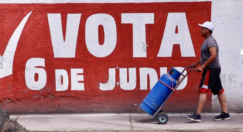 Transeúntes pasan frente a propaganda electoral en Ciudad de México. EFE/Carlos Ramírez