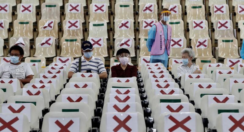 Varias personas esperan tras recibir una dosis de AstraZeneca durante una vacunación masiva en la ciudad tiwanesa de Nuevo Taipei. EFE/ Ritchie B. Tongo