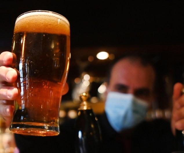 Un camarero ofrece una pinta en un pub de Londres. EFE/EPA/Andy Rain.