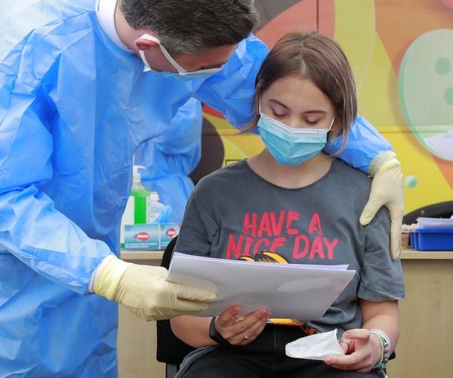 Una niña recibe un diploma tras ser inmunizada en Bucarest el primer día de vacunación infantil contra la covid-19 en Rumanía. EFE/EPA/Robert Ghement