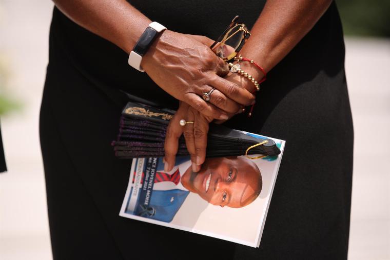 Una asistente sujeta una fotografía de Jovenel Moise durante una ceremonia en honor al asesinado presidente haitiano en los jardines del Museo Panteón Nacional de Haití (MUPANAH), en Puerto Príncipe. EFE/ Orlando Barría